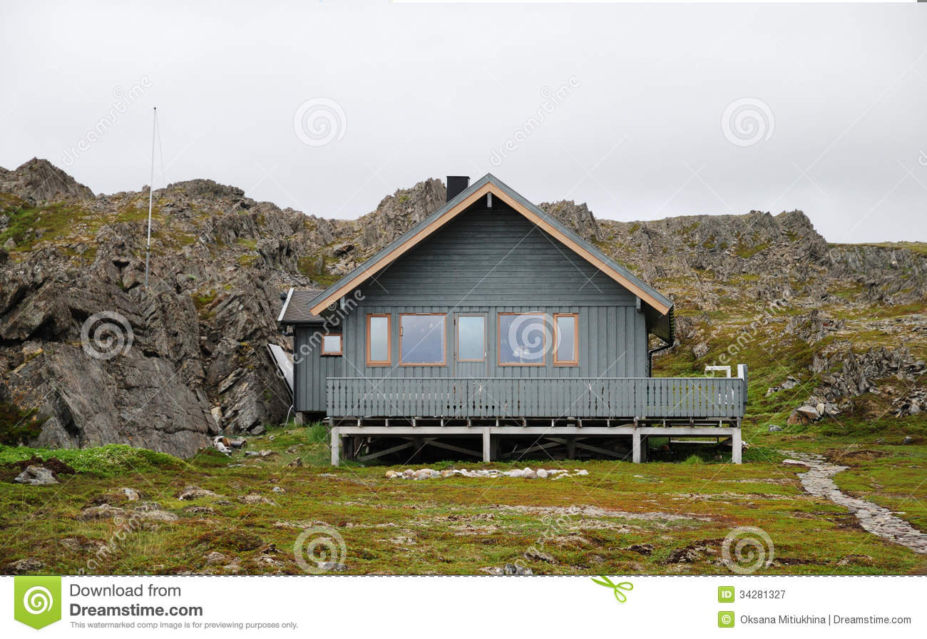 Norwegian Wooden House On Stilts Under Cliff Royalty Free