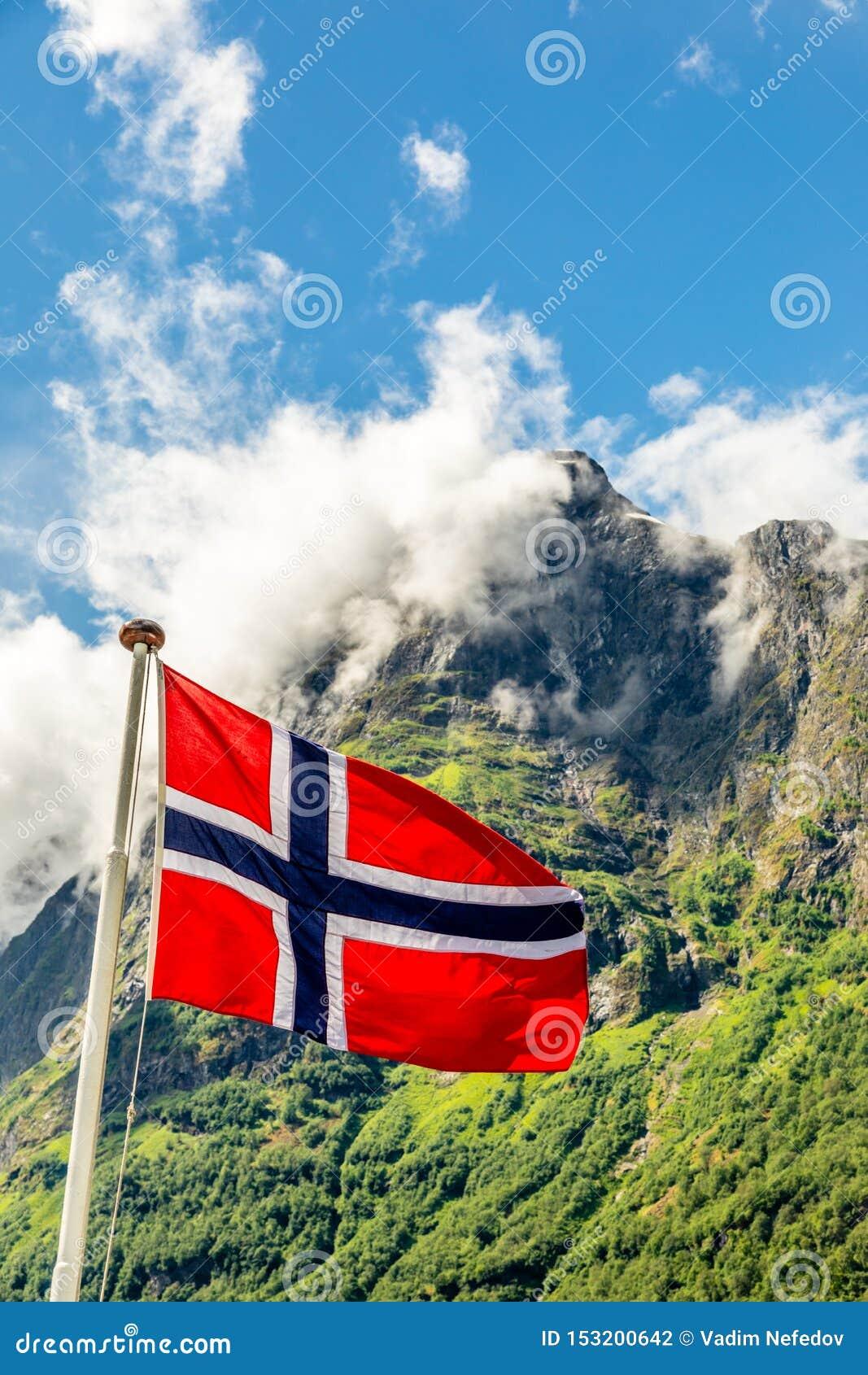 Norwegische Staatsflagge, die in den Wind und in das mountain& x27 wellenartig bewegt; s-Spitze in Neroy-Fjord, Aurlan, Sogn-og F