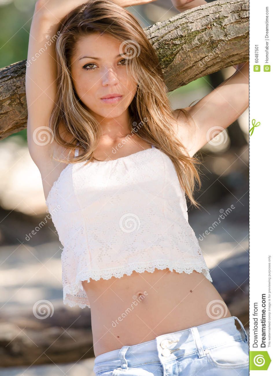 Nostalgic moments of a beautiful girl as she rests on a tree trunk