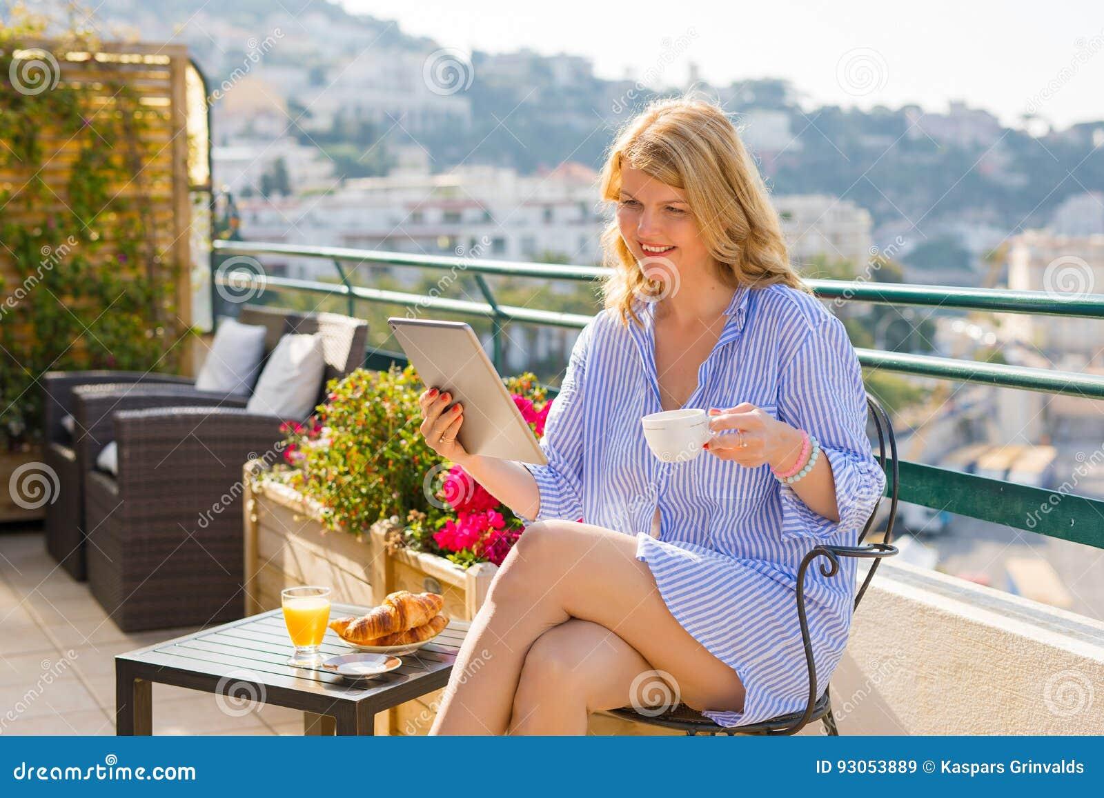 Notícia da manhã da leitura da mulher na tabuleta ao comer o café da manhã