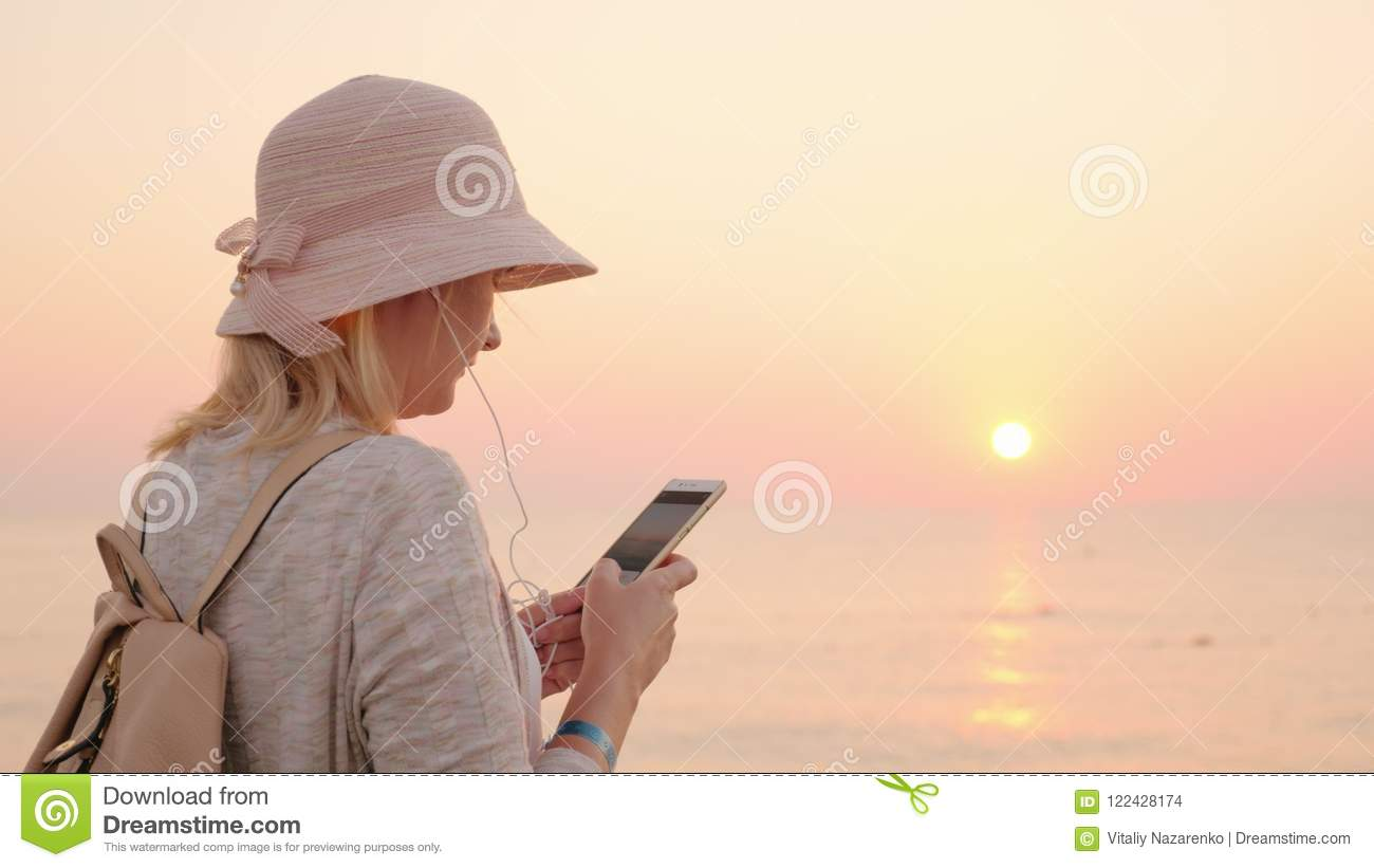 Not a minute without a phone, the girl is standing on the beach with a pink sky and sky, looking at the phone screen and