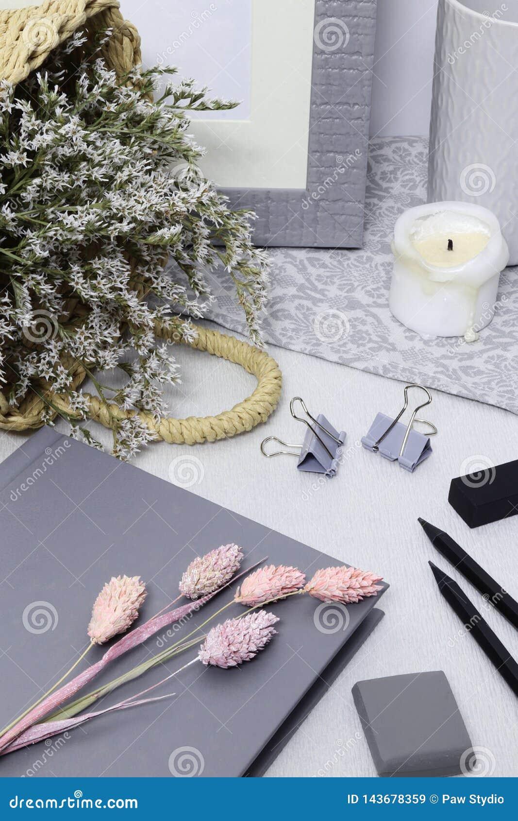 Nota cinzenta com quadro, as flores brancas e os lápis