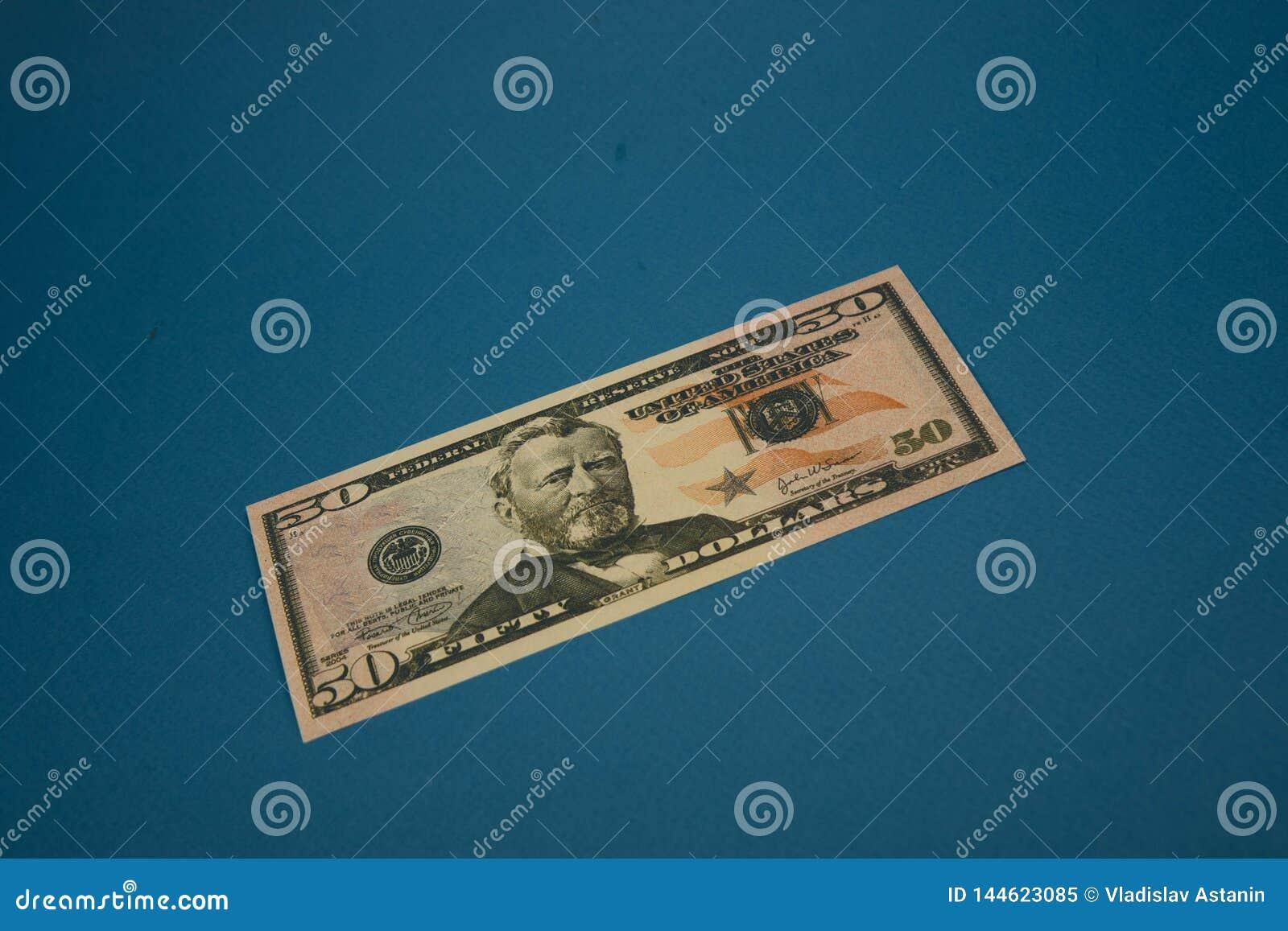 Nota de dólar isolada do americano cinqüênta no fundo azul
