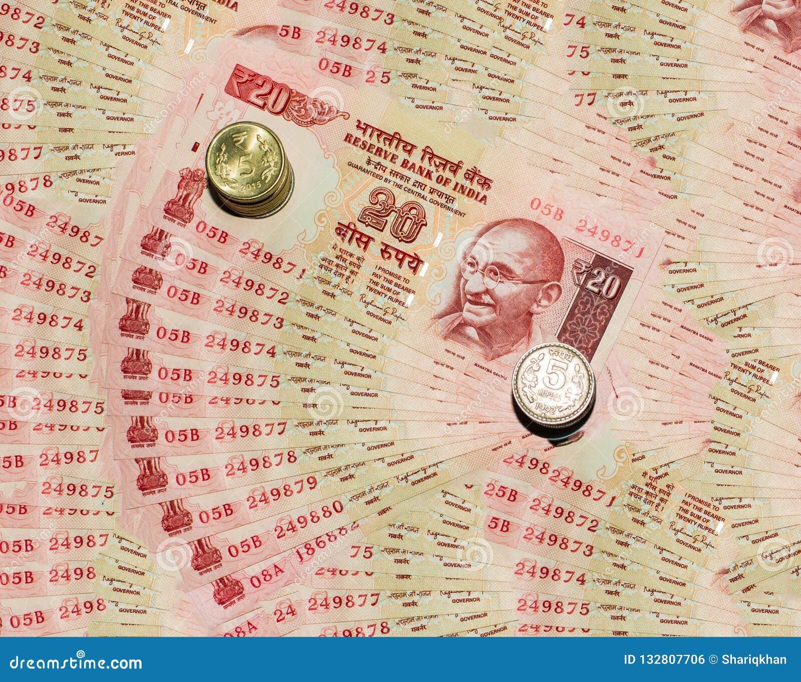 Nota india de la moneda 20 rupias y monedas con el fondo