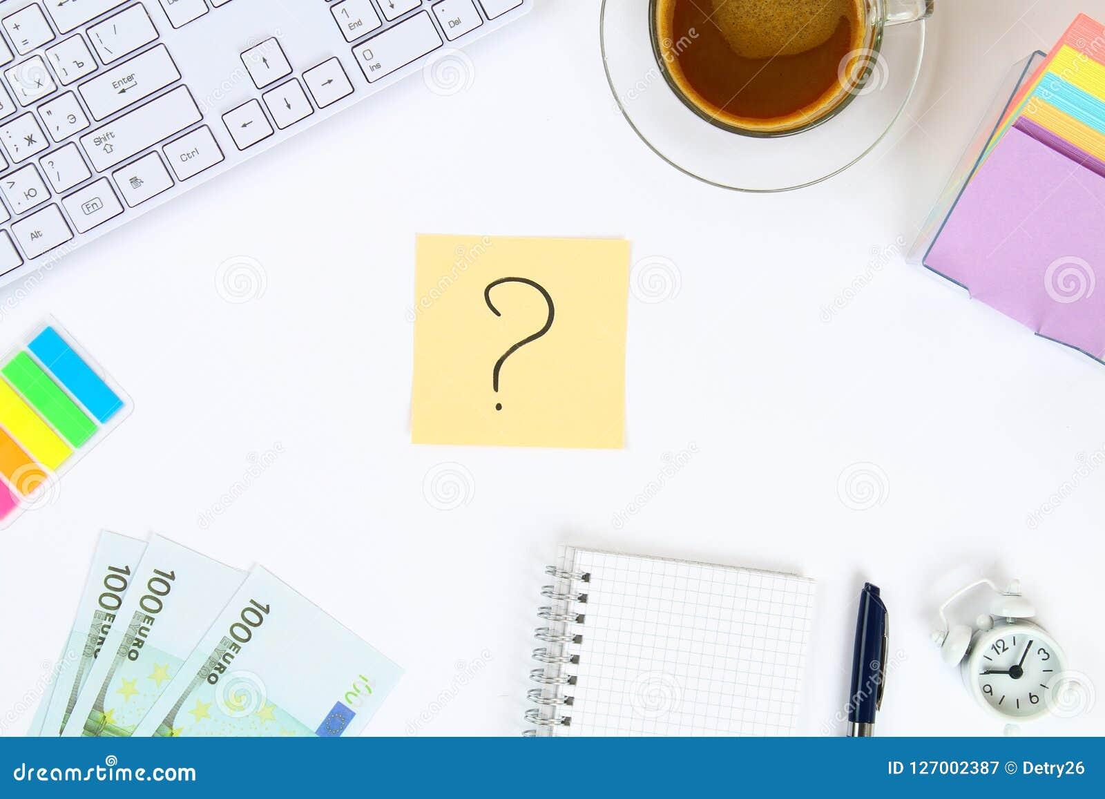 Nota multicolore degli autoadesivi con il punto interrogativo sul desktop bianco accanto ad una tazza di caffè e della tastiera