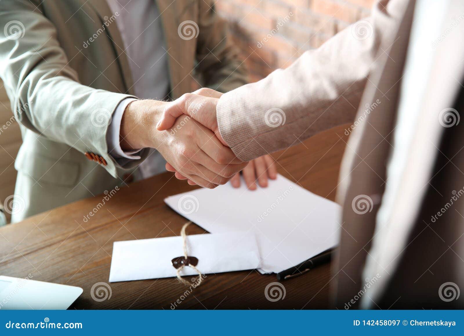 Notarius publicu och klient som i regeringsställning skakar händer, closeup
