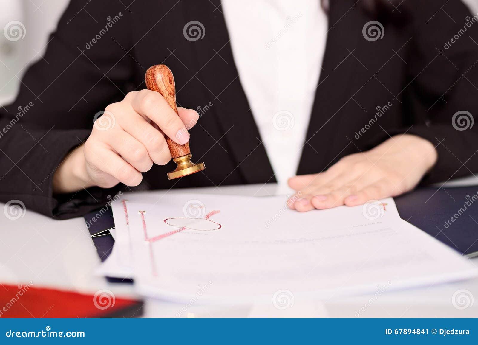 Notariusza społeczeństwa kobiety ręki stempluje notariusza akt