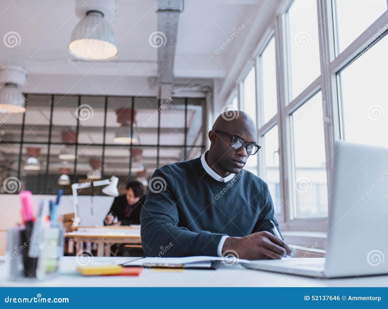 Notas africanas de la escritura del hombre mientras que trabaja en un ordenador portátil