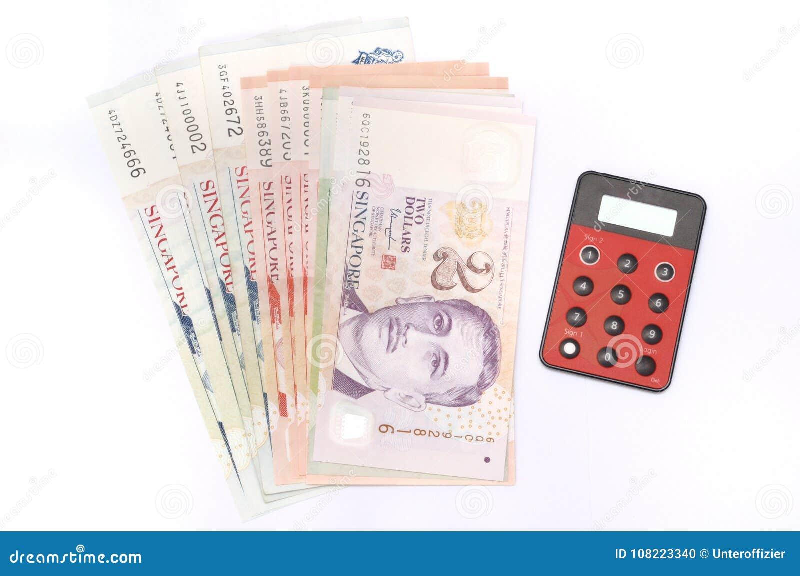 Notas do dólar de Cingapura com um dispositivo dos Internet banking