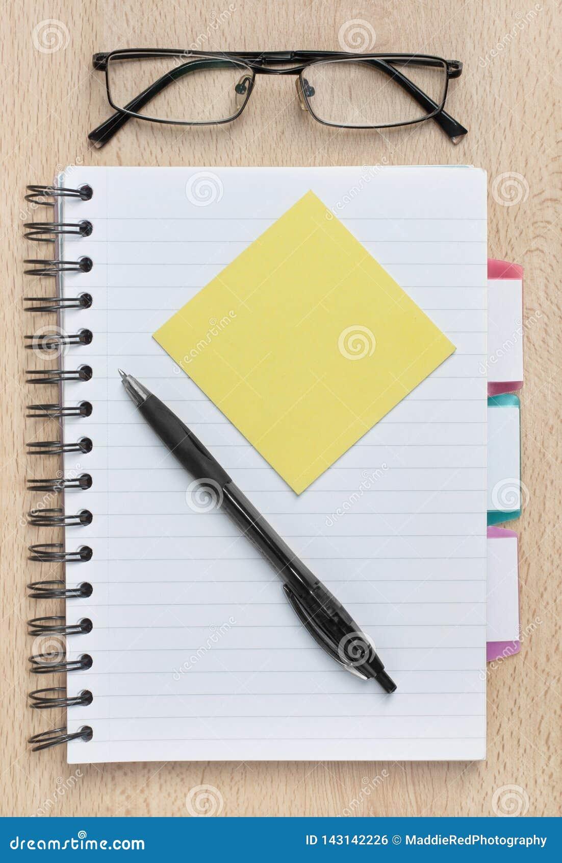Notatnik z pustą kleistą notatką na domowym biurku z kopii przestrzenią lub biurze,