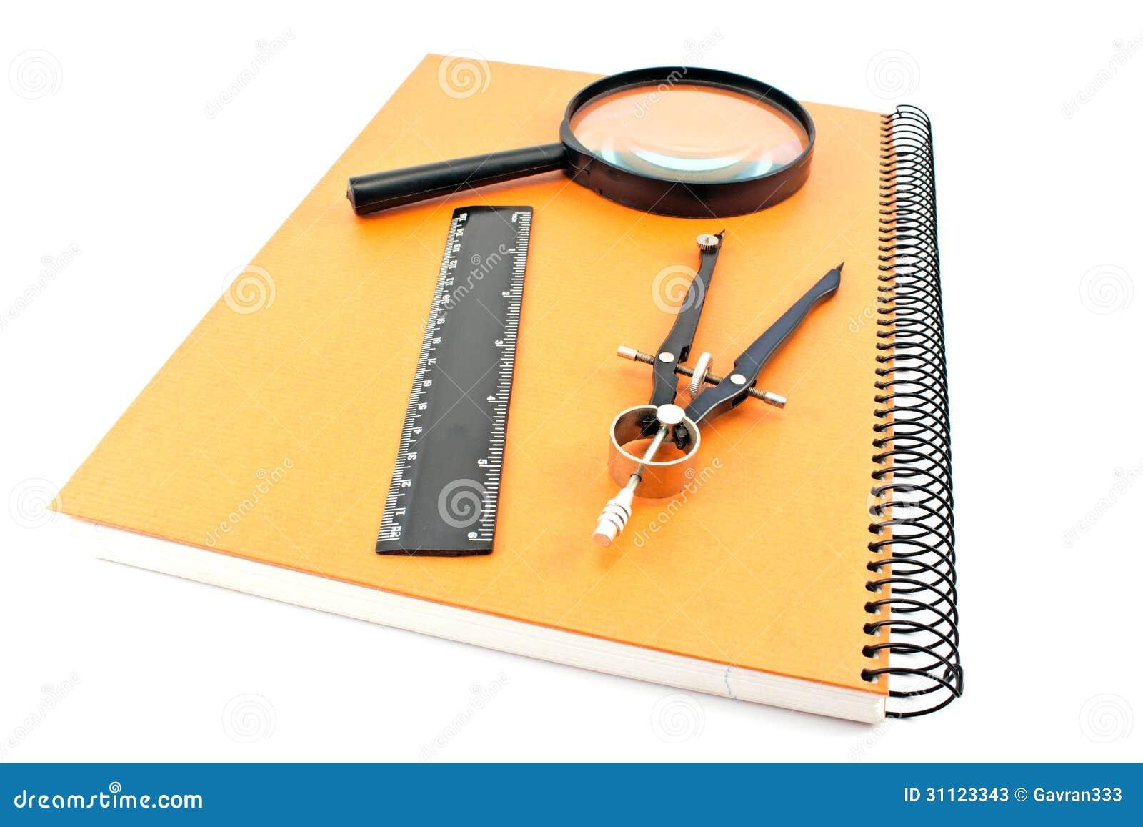 Notatnik z rysunkowym kompasem, władcą i magnifier,
