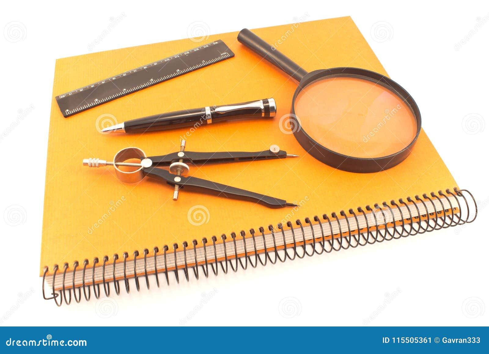 Notatnik z rysunkowym kompasem, władcą i magnifier odizolowywającymi na w,