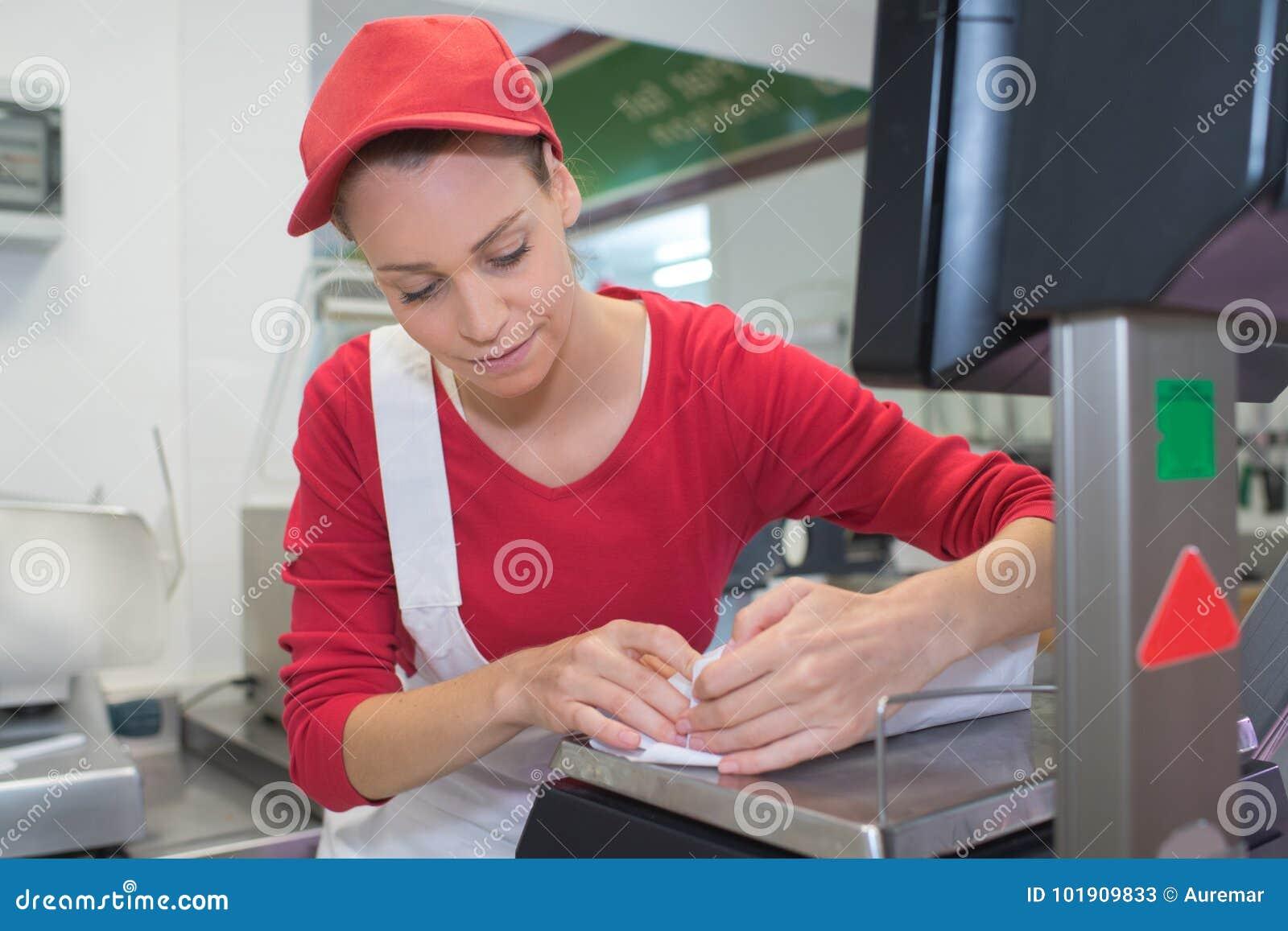 Note heureuse d écriture de vendeuse au compteur dans la boucherie