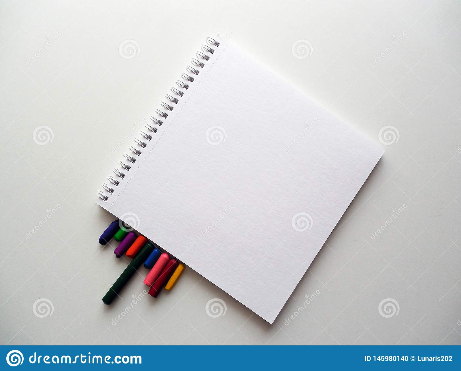 Notebook and coloured crayons in white