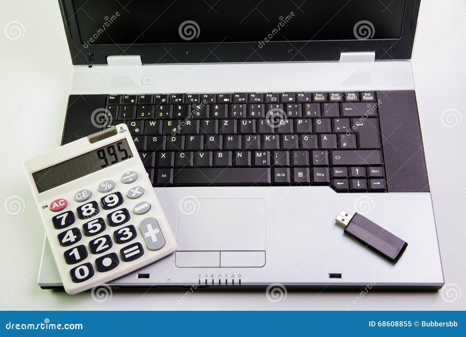 Notebook computer on the desk.Calculators,USB flash drive stick