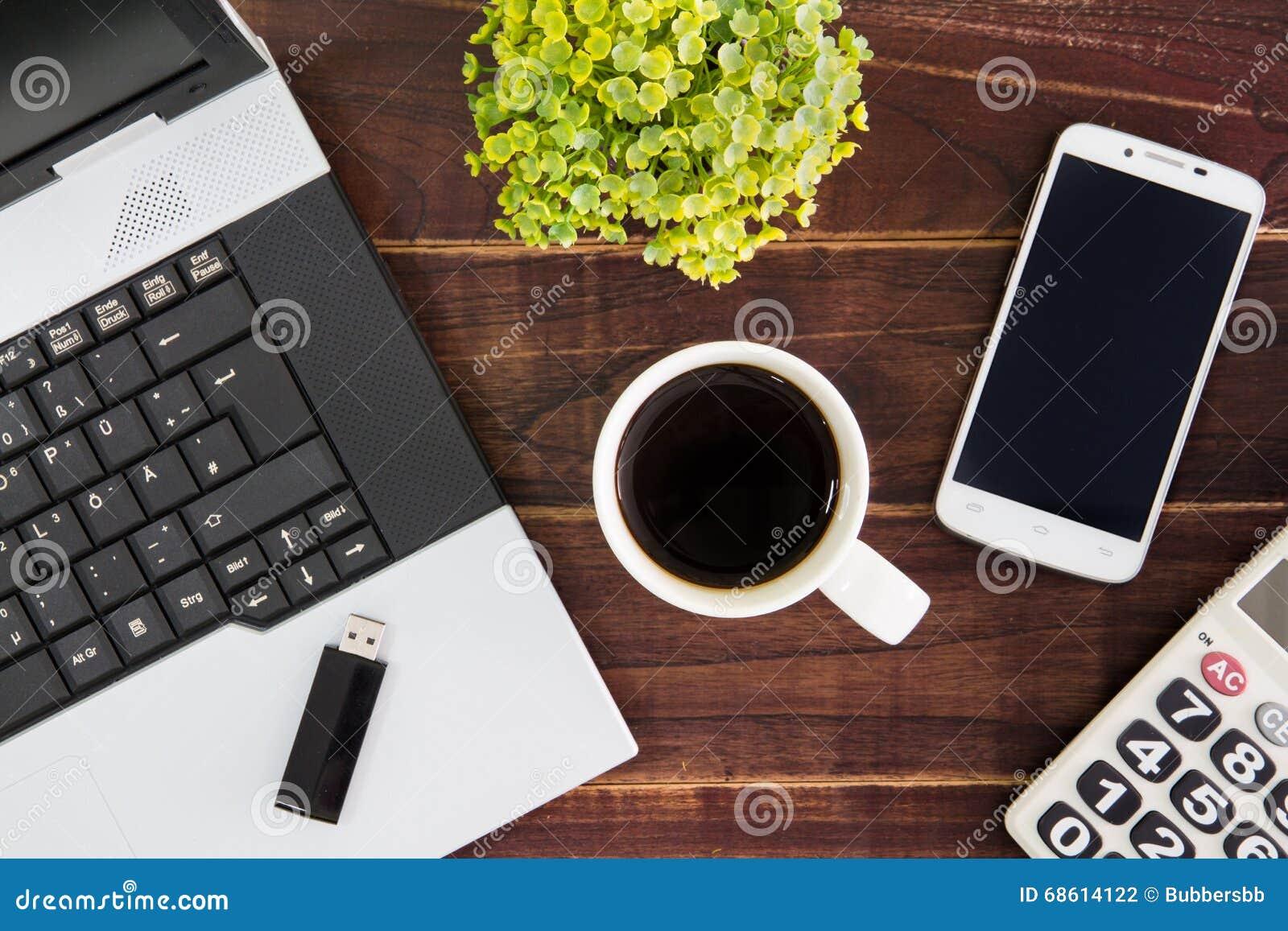 Notebook computer on the desk.Calculators,USB flash drive stick,coffee cup,smartphone