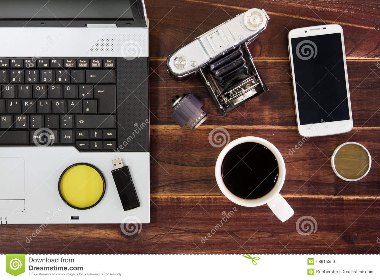 Notebook computer on the desk.USB flash drive stick,coffee cup,camera,smartphone
