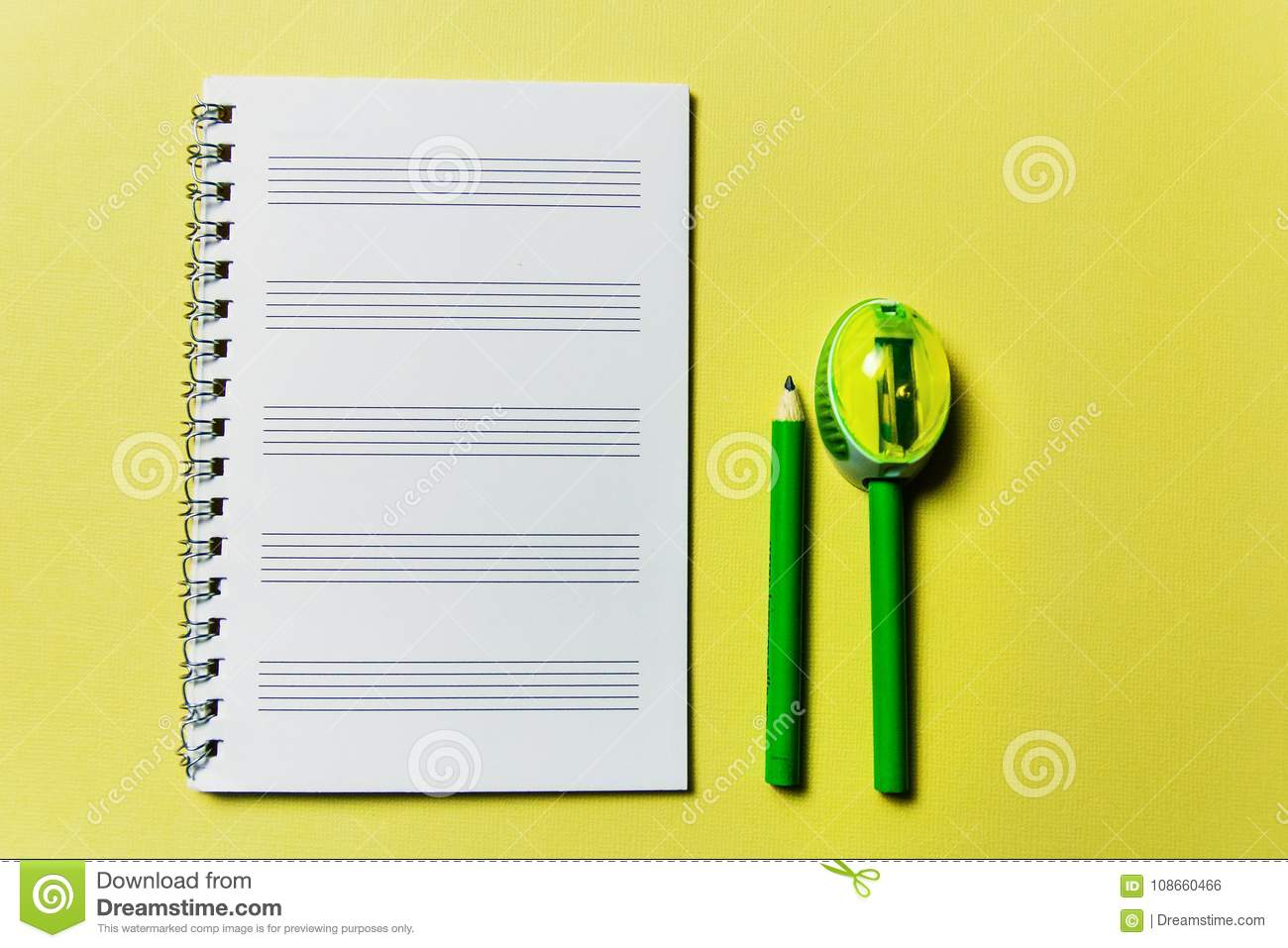 notebook and a green pencil and pencil sharpener on yellow