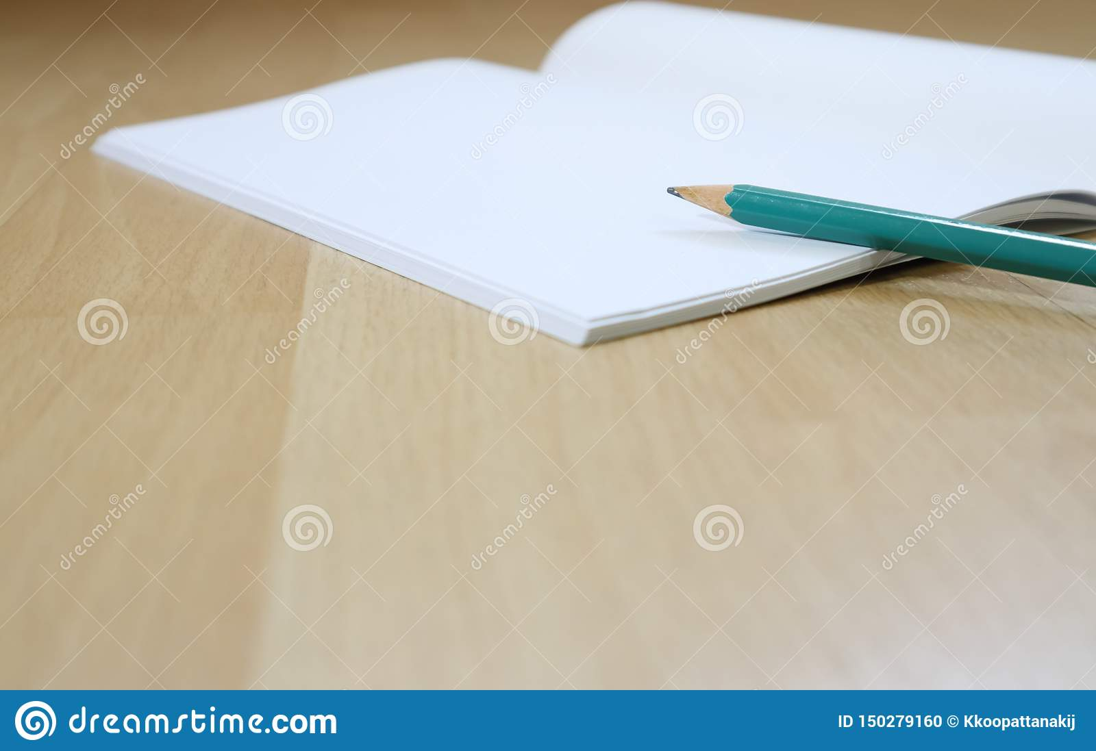 Notebook and pen cil on the wooden floor