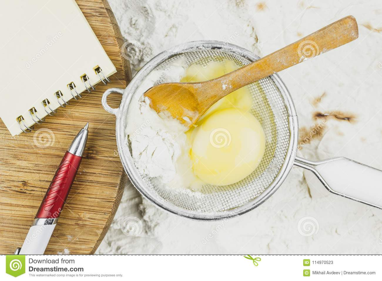 Notebook for recipes, egg, wooden spoon on a background of flour.