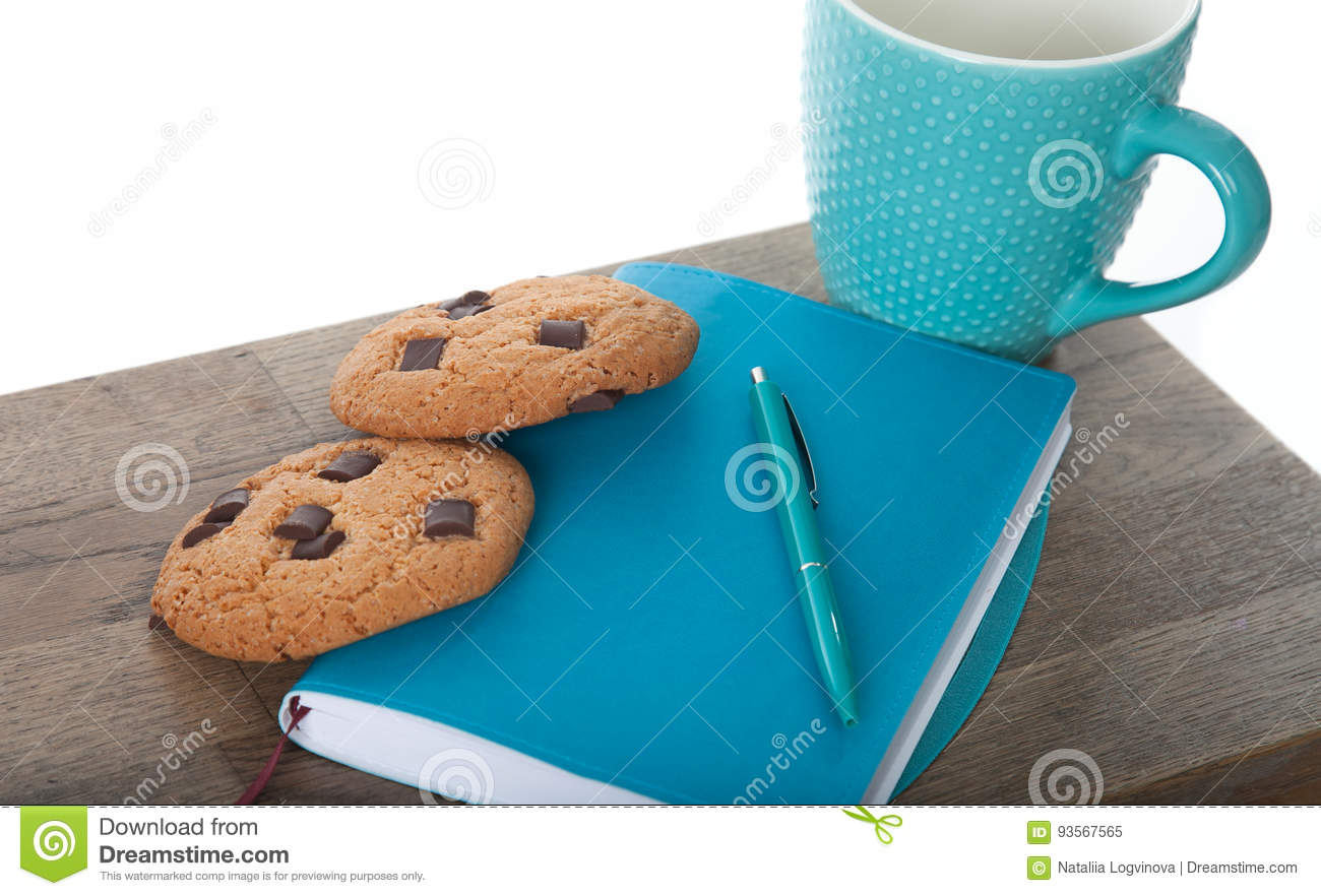 Notepad, cup, pen in turquoise color with chocolate chip cookies. wooden table and white background. Great morning and start of th