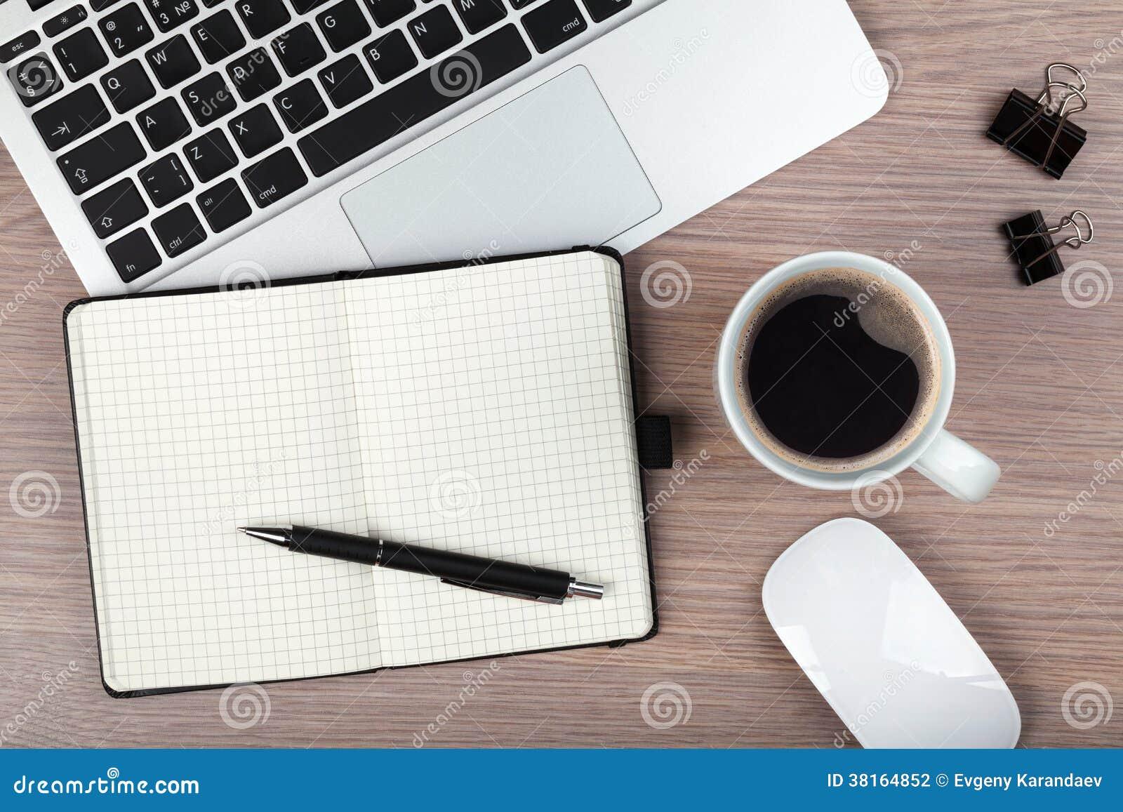 Notepad, laptop i filiżanka na drewno stole,