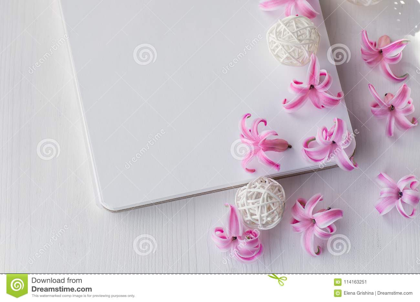 Notepad na białym drewnianym tle Różowy hiacynt kwitnie na stole