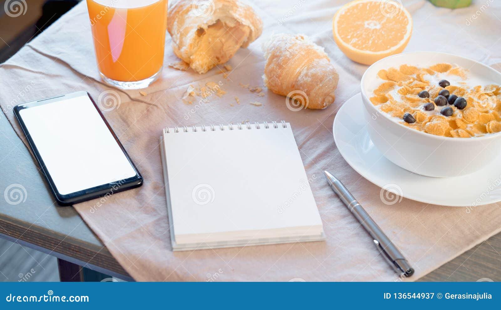 Notepad och mobiltelefon med den tomma skärmen nära den sunda frukosten