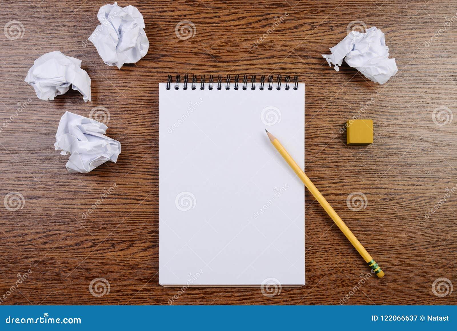 Notepad på en trätabell och skrynkliga ark omkring Lekmanna- lägenhet