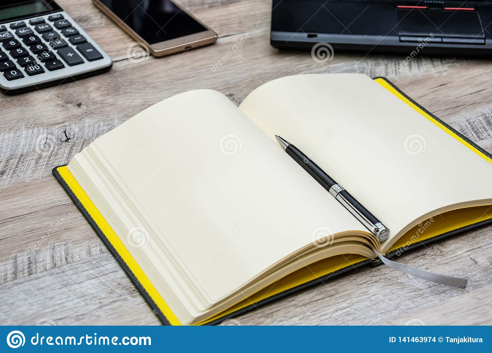 Notepad, pen, smartphone and part of the laptop on a wooden background
