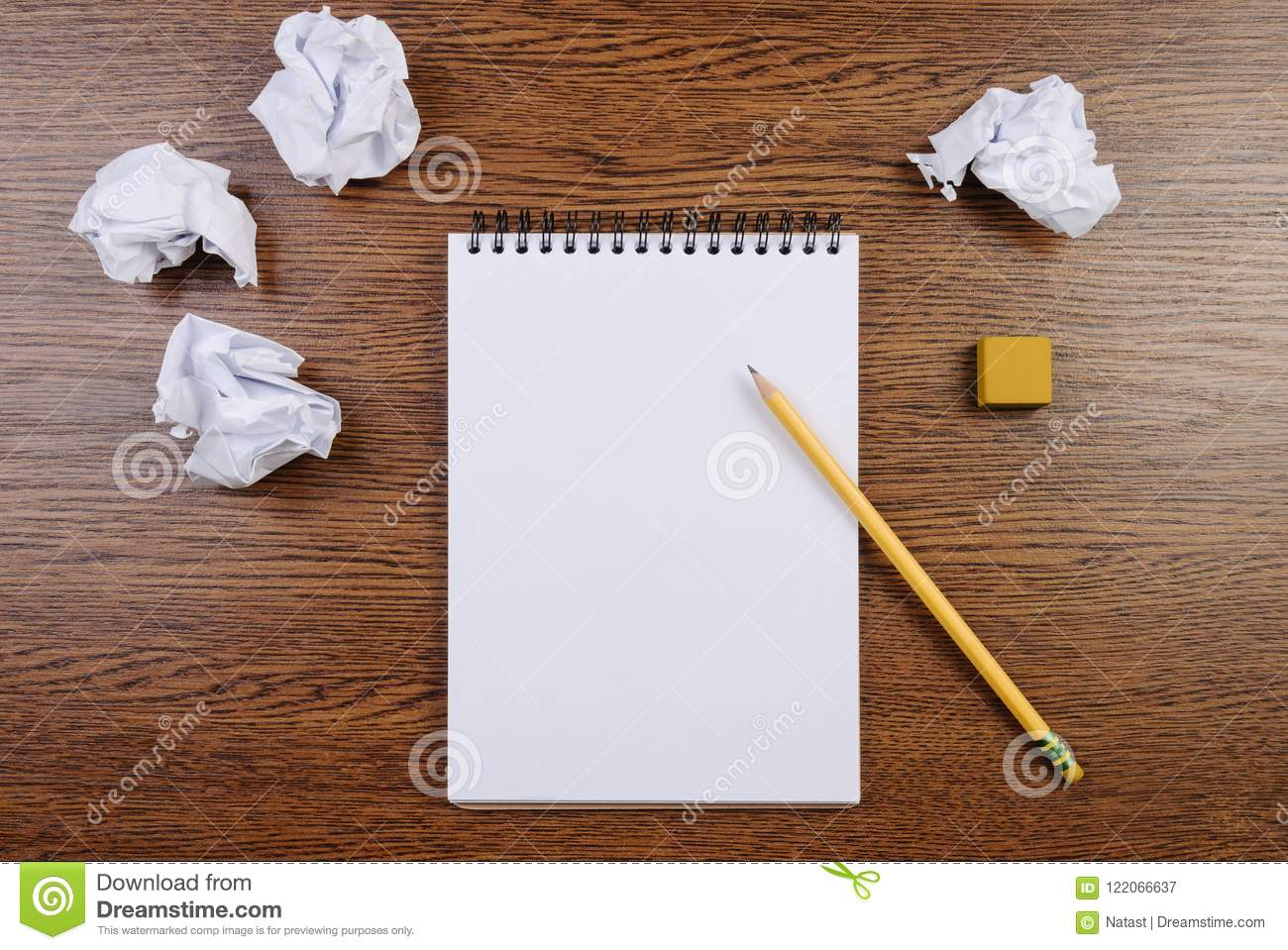 Notepad on a wooden table and crumpled sheets around. Flat lay.