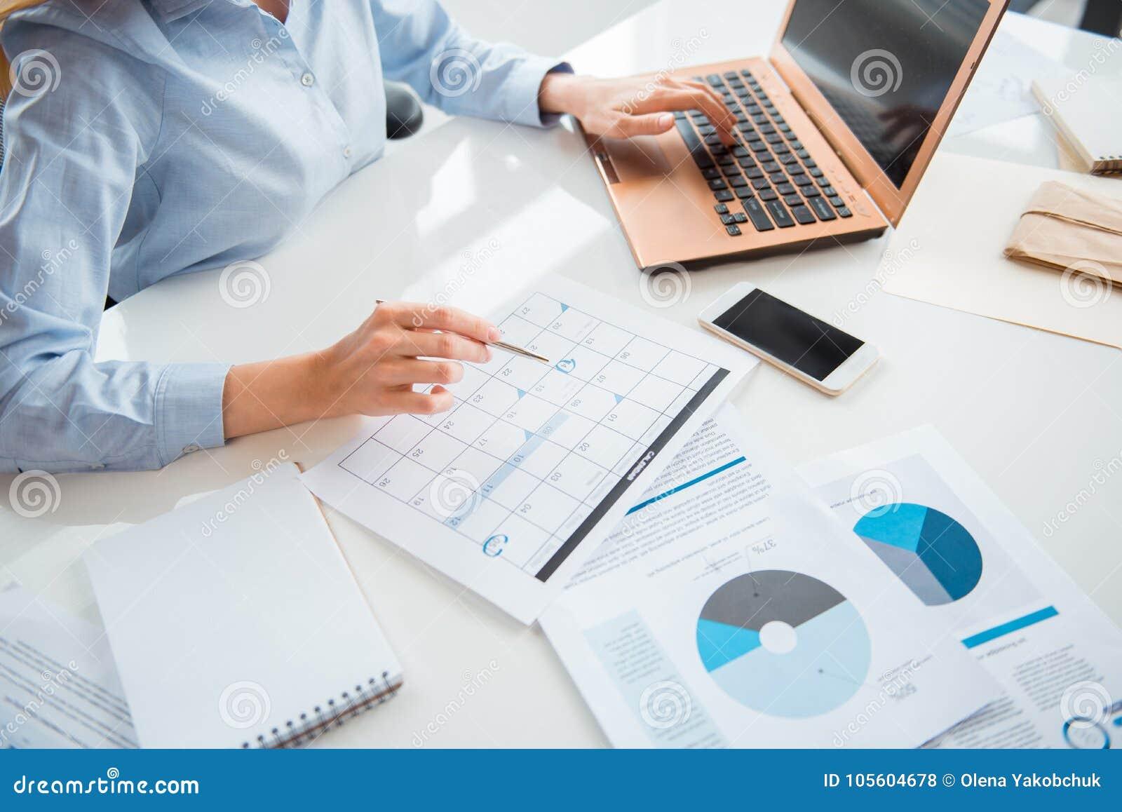 Notes d inscription de main de femme d affaires sur le calendrier