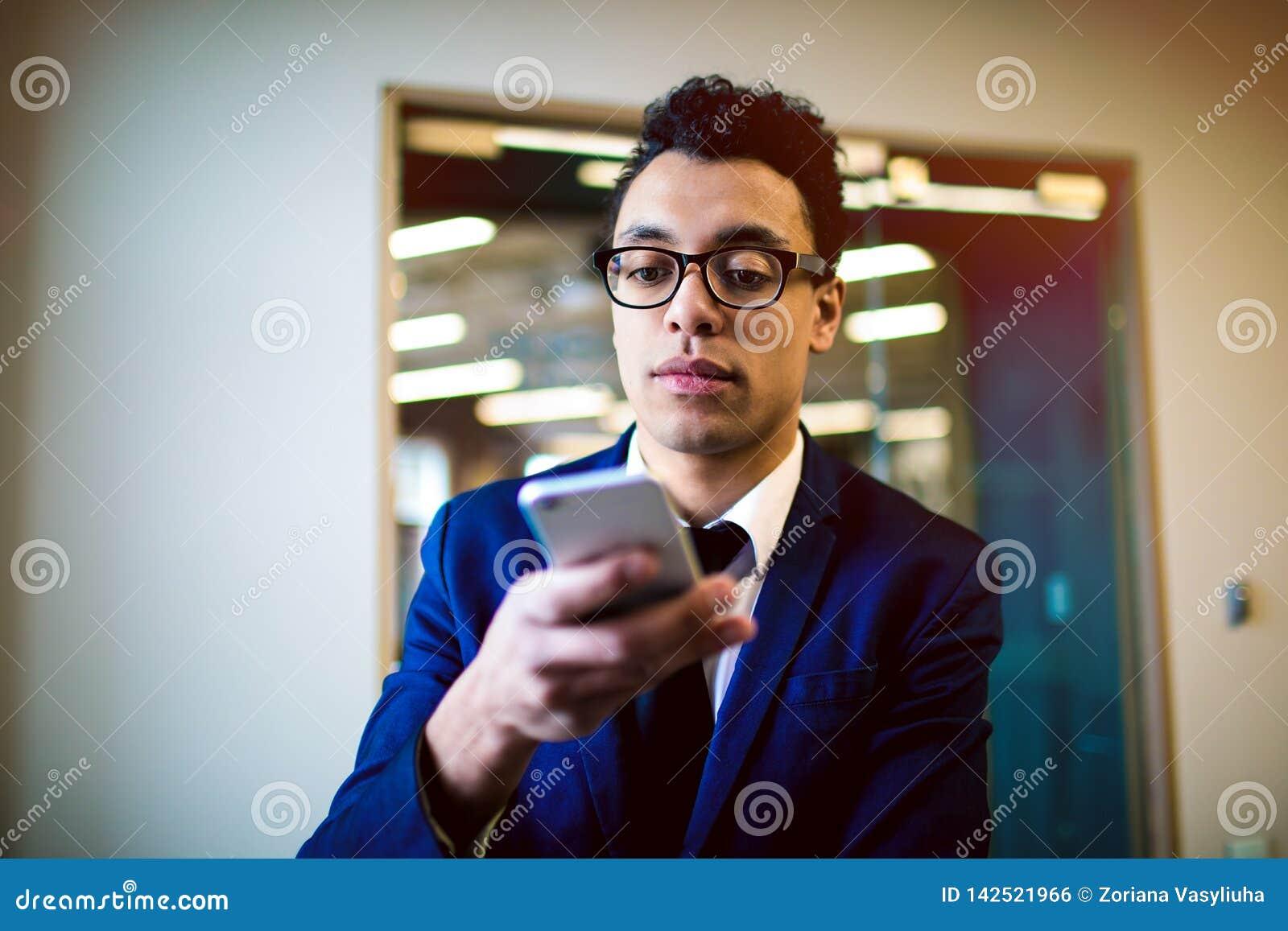 Notificación de lectura orgullosa masculina del jefe en el teléfono móvil Abogado en texto que mecanografía del traje en el teléf