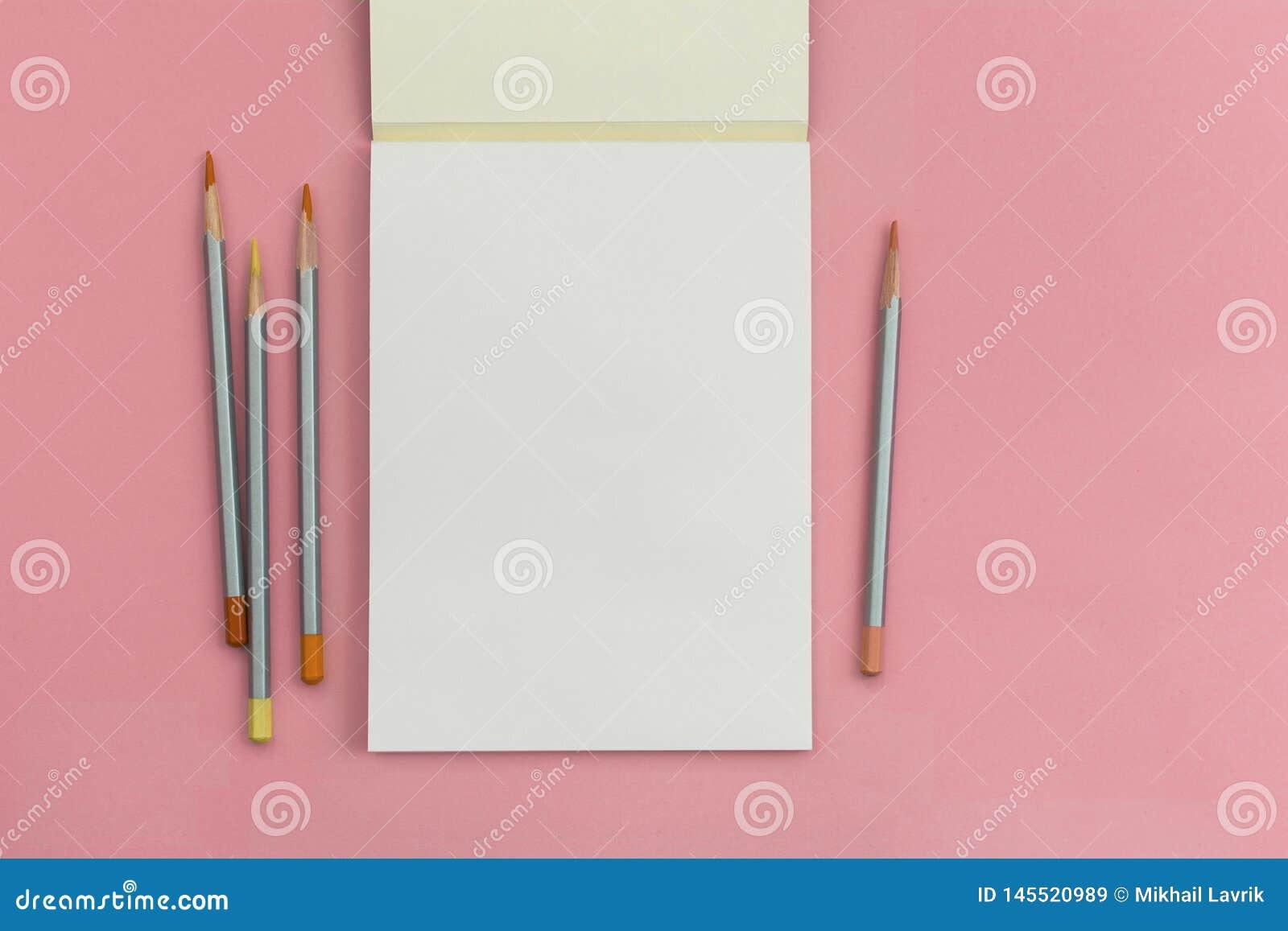 Notitieboekje met een potlood op een roze achtergrond