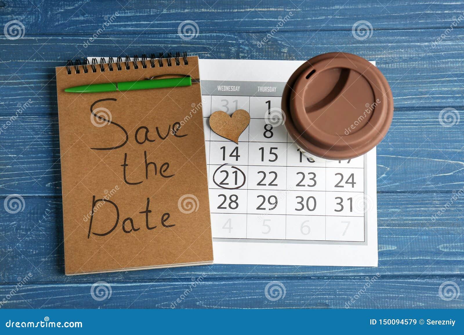 """Notitieboekje met inschrijving  """"sparen de Datum """", kalender en kop op kleuren houten achtergrond"""