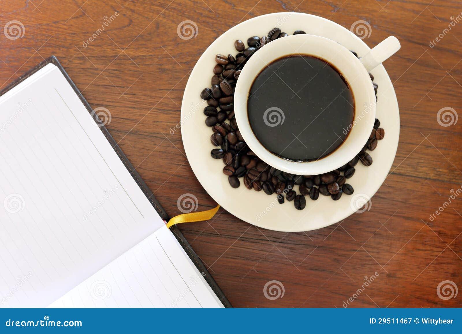 Notitieboekje met koffiekop op grungehout