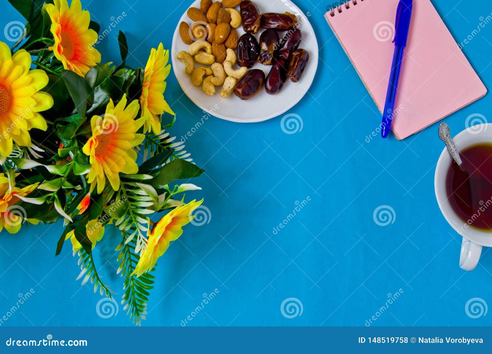 Notitieboekje, pen, bloemen en een Kop thee, vrouwelijke werkplaats