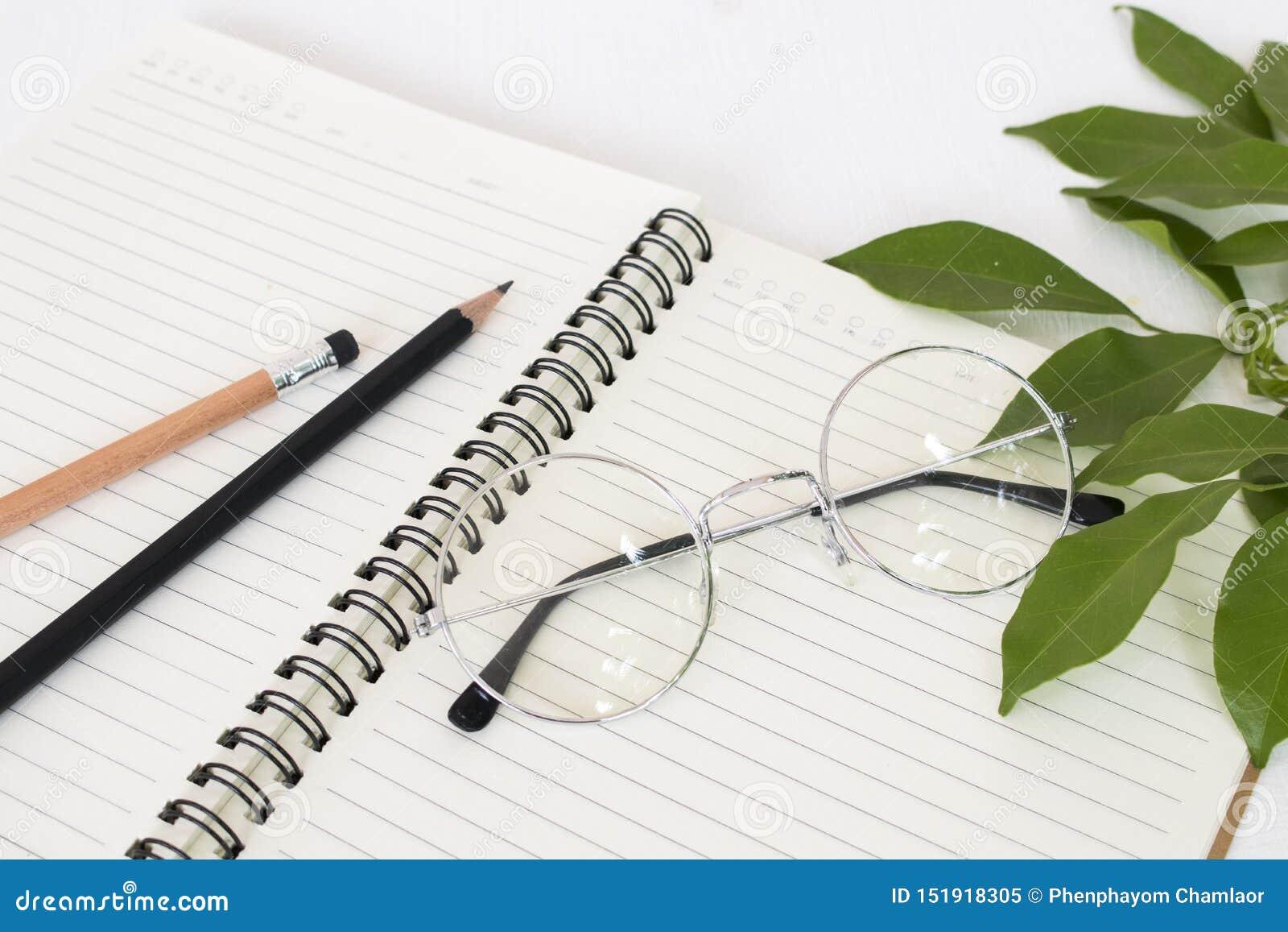 Notitieboekje voor mededeling met potlood, bril