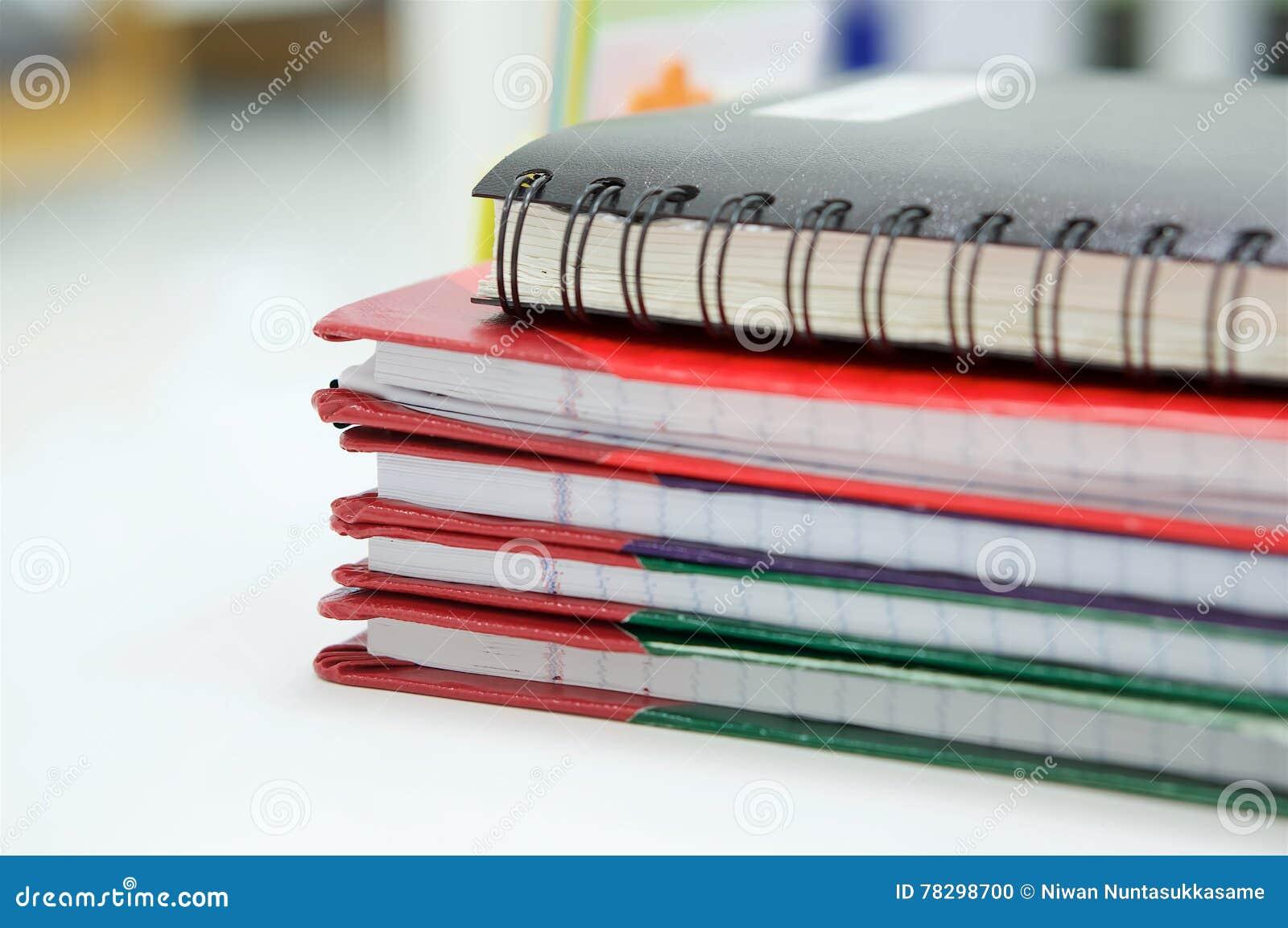 Notizbuch und Stapel des Berichtsbuches im Büro