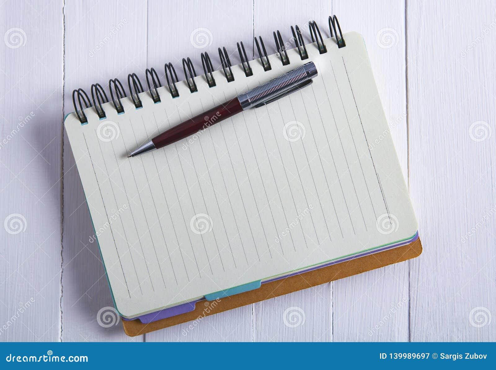 Notizbuchstift auf hölzernem Hintergrund
