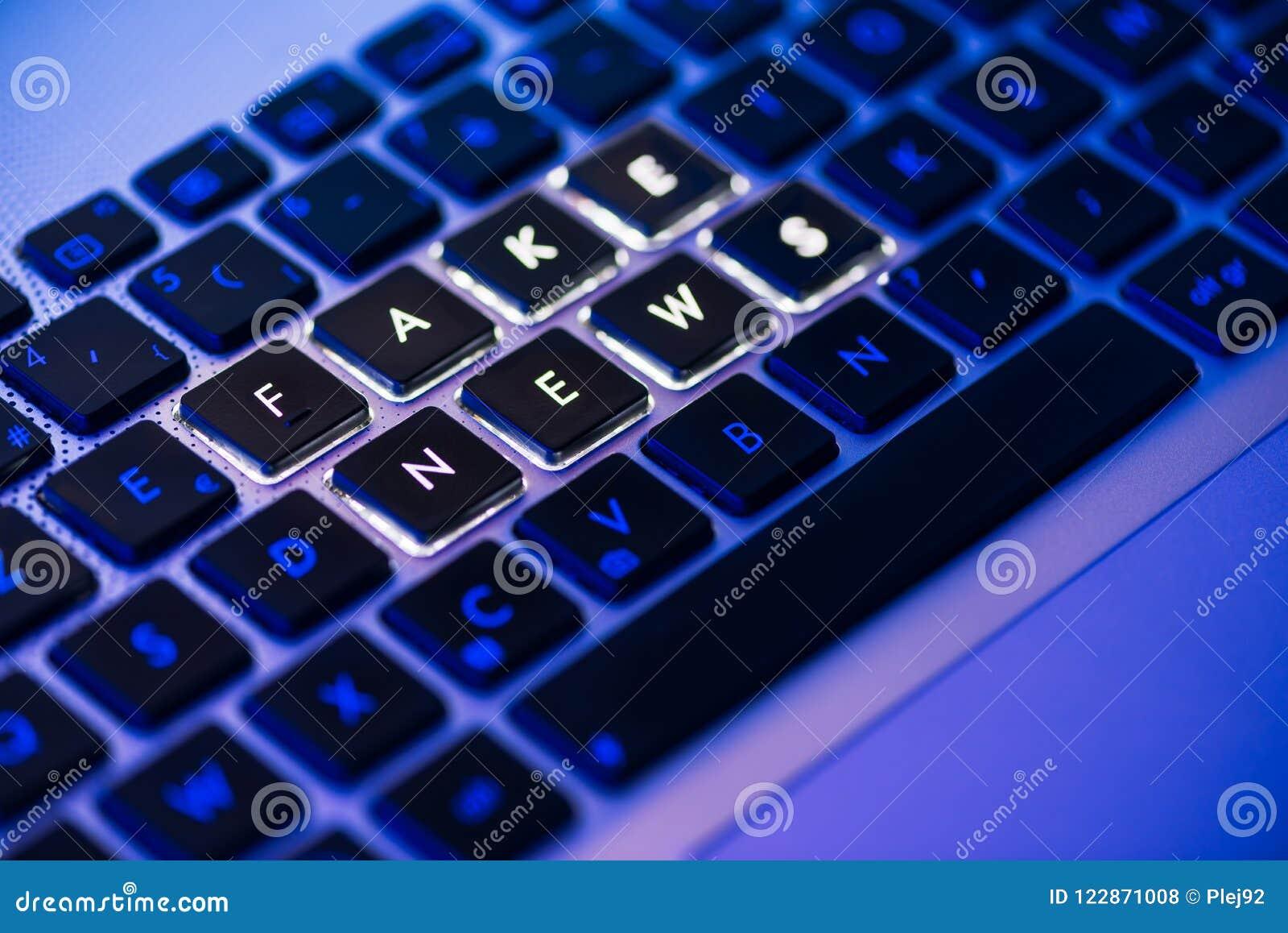 Notizie false scritte su una tastiera retroilluminata in una luce ambiente blu