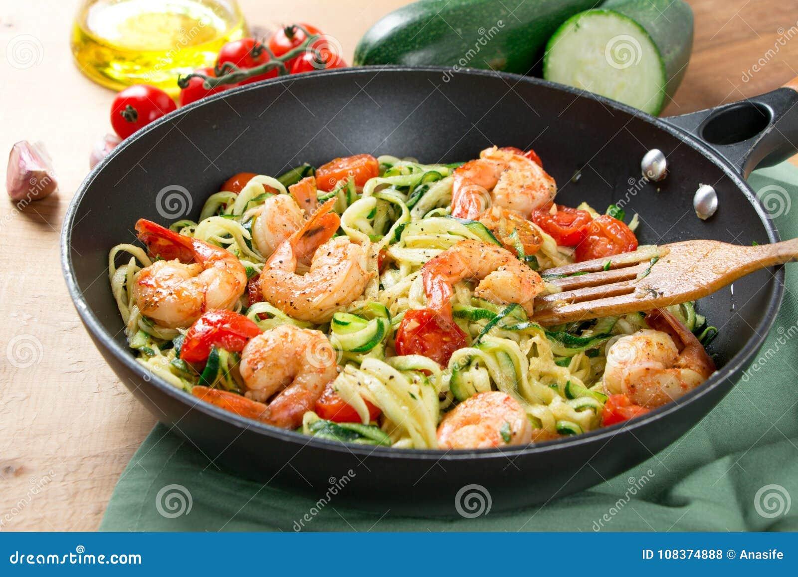 Nouilles de courgette faites sauter avec la tomate-cerise et les crevettes roses dans une casserole