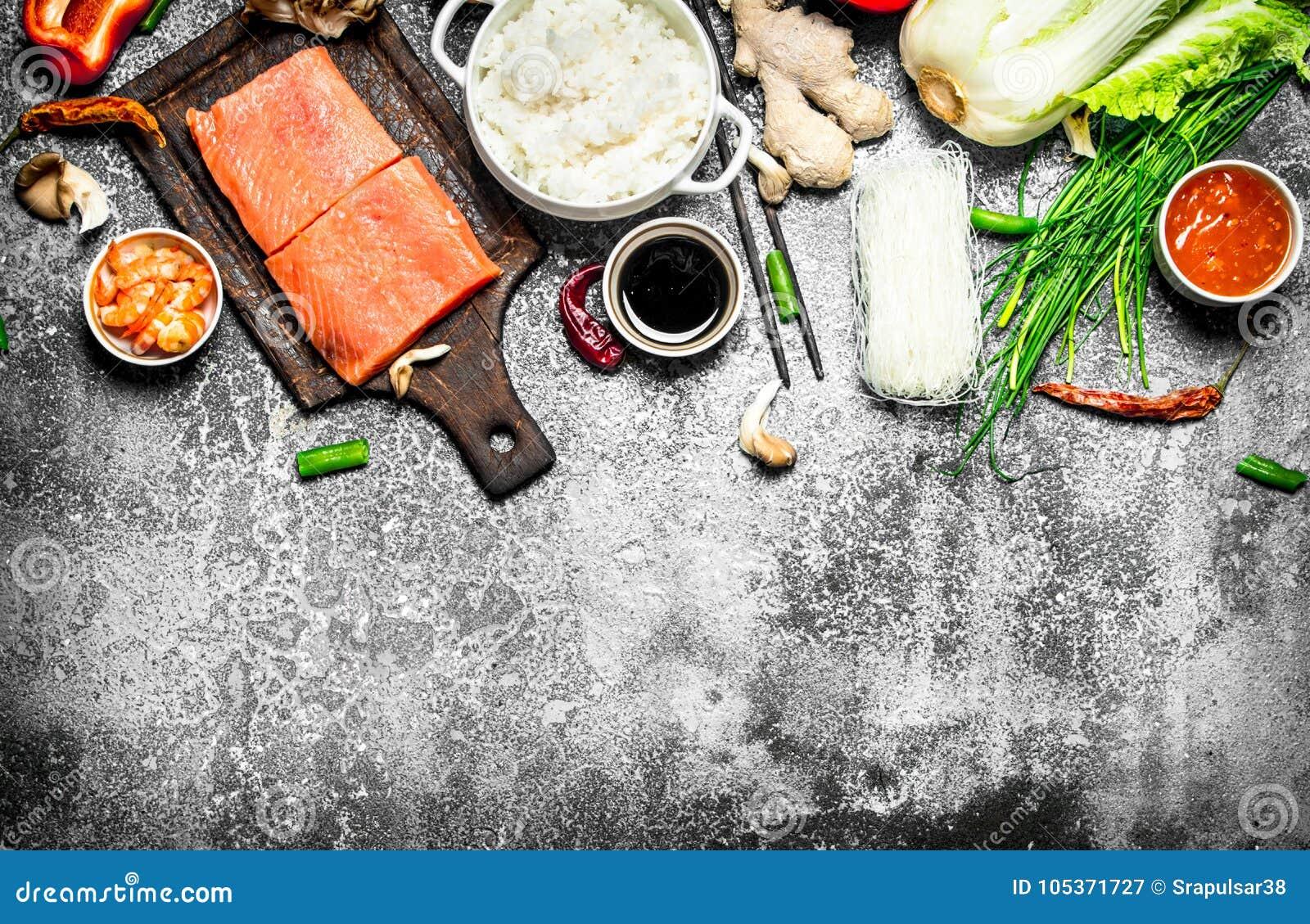 Nourriture asiatique Riz bouilli avec un morceau de saumons et d un grand choix d ingrédients Sur le fond rustique