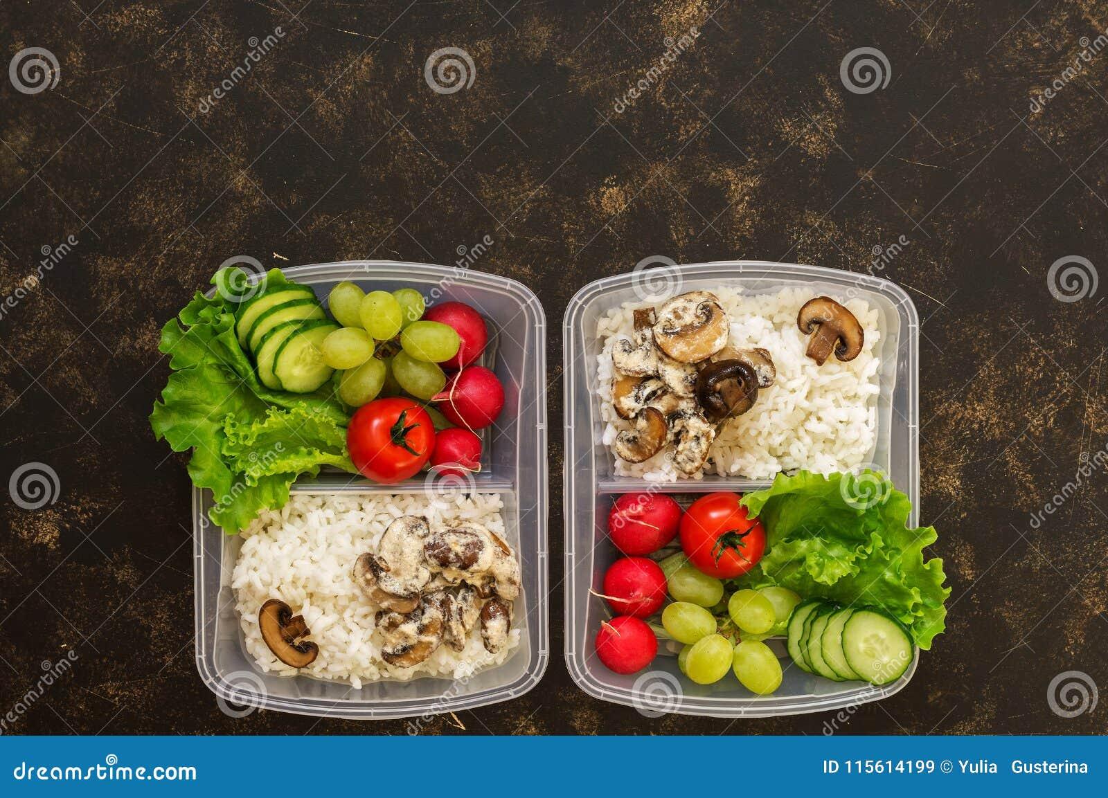 Nourriture dans des récipients, le riz avec des champignons et la légume-laitue fraîche, radis, raisins, concombres, tomates Le f