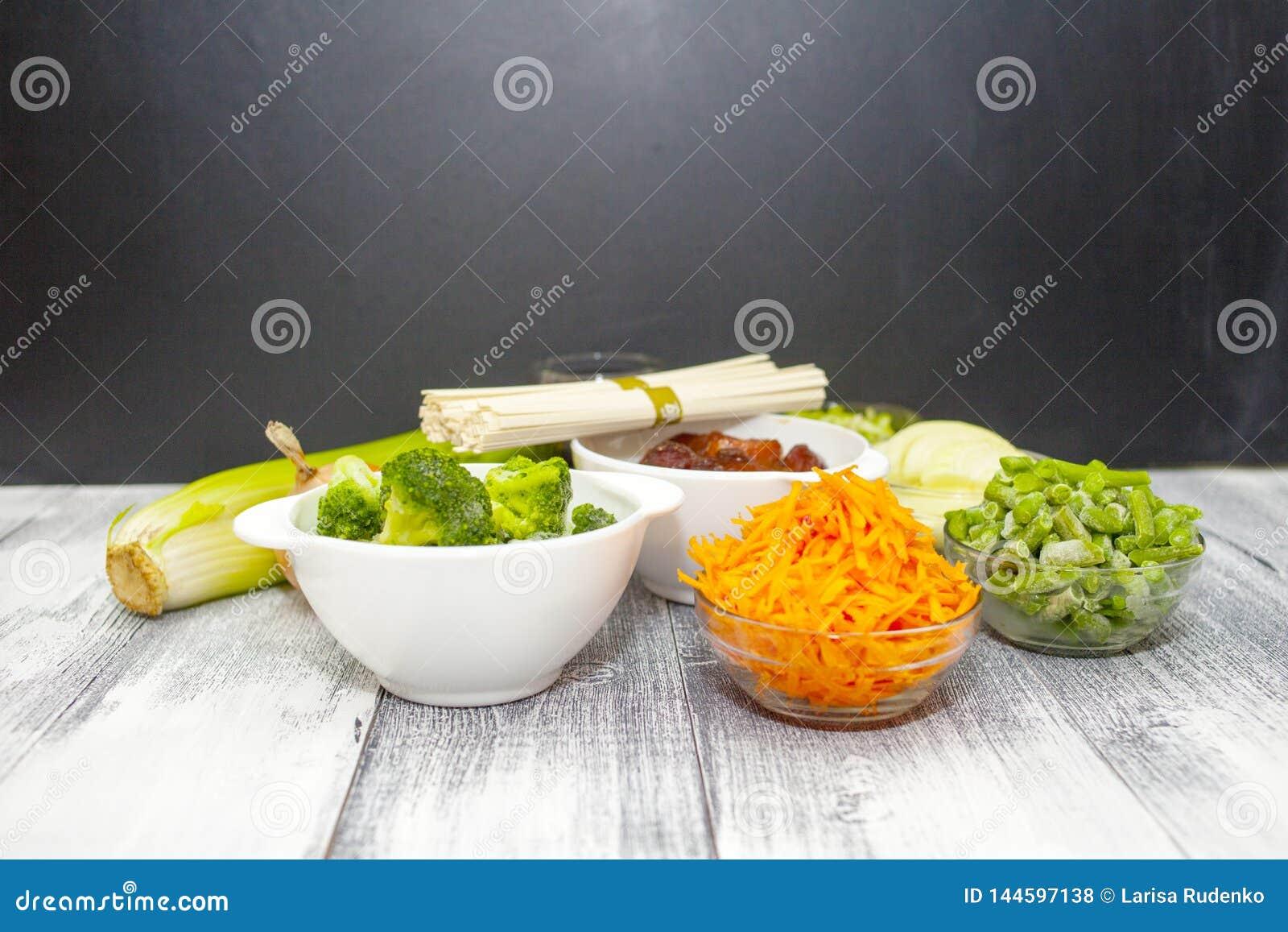 Nourriture de chinois traditionnel - nouilles d Udon avec du porc et des légumes en sauce à teriyaki sur un conseil en bois Ingré