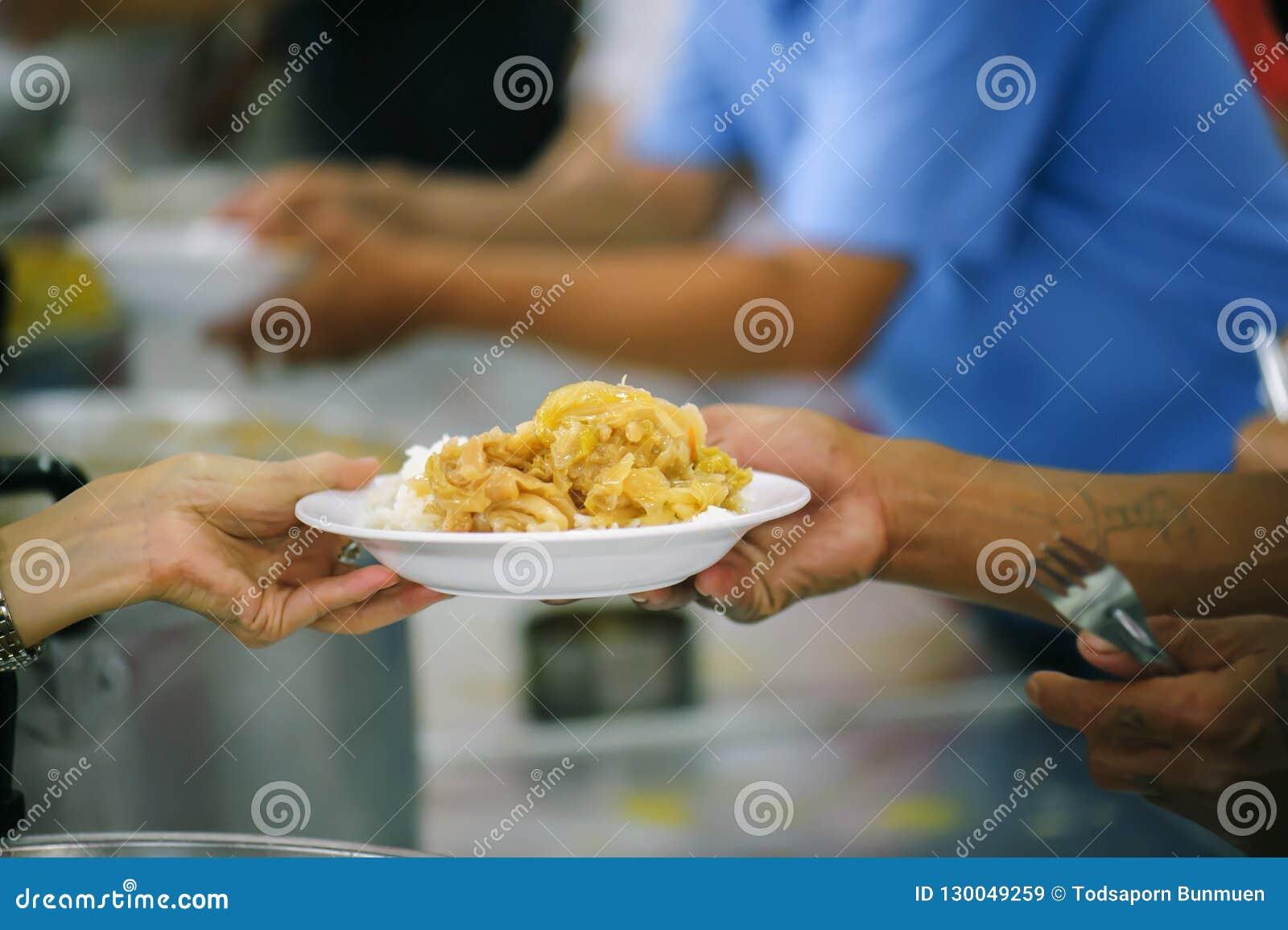 Nourriture de part de volontaires aux pauvres pour soulager la faim : Concept de charité