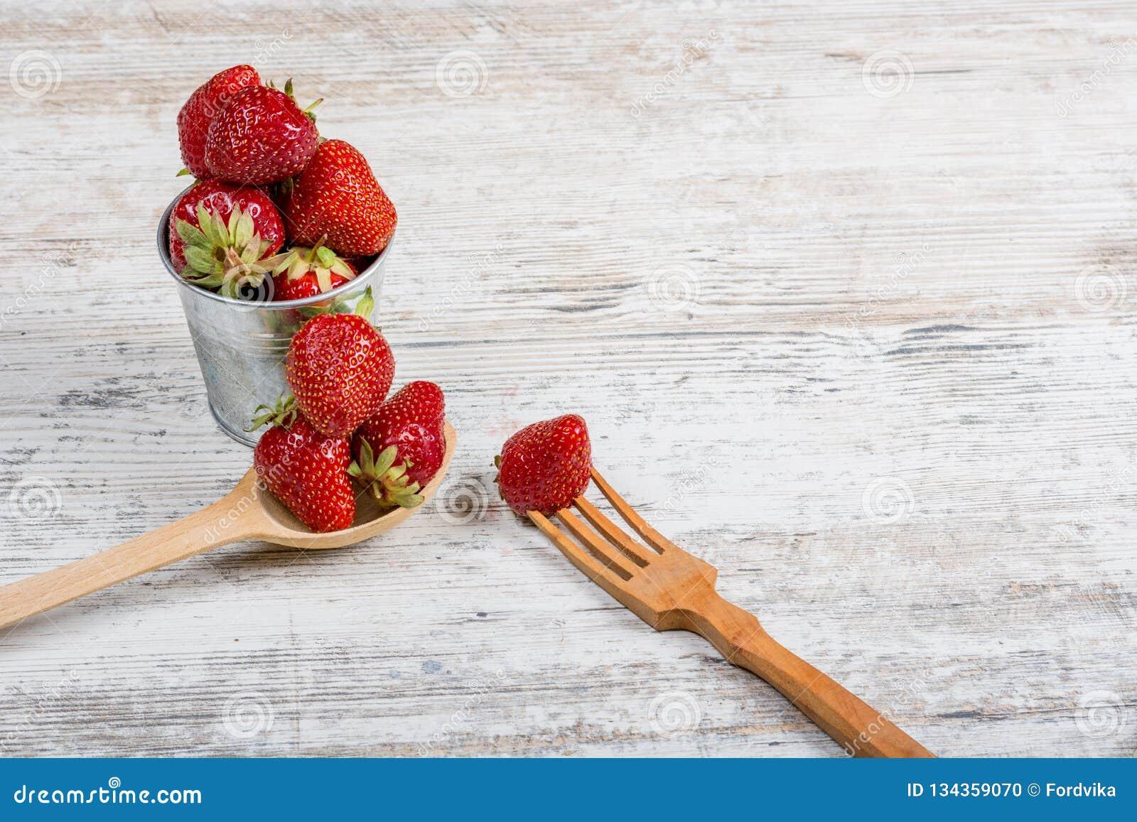 Nourriture de vitamine d été Un seau de fraises parfumées mûres fraîches et une cuillère et une fourchette en bois
