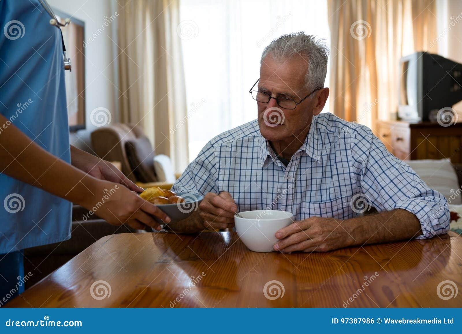 Nourriture femelle de portion de docteur à l homme supérieur dans la maison de repos