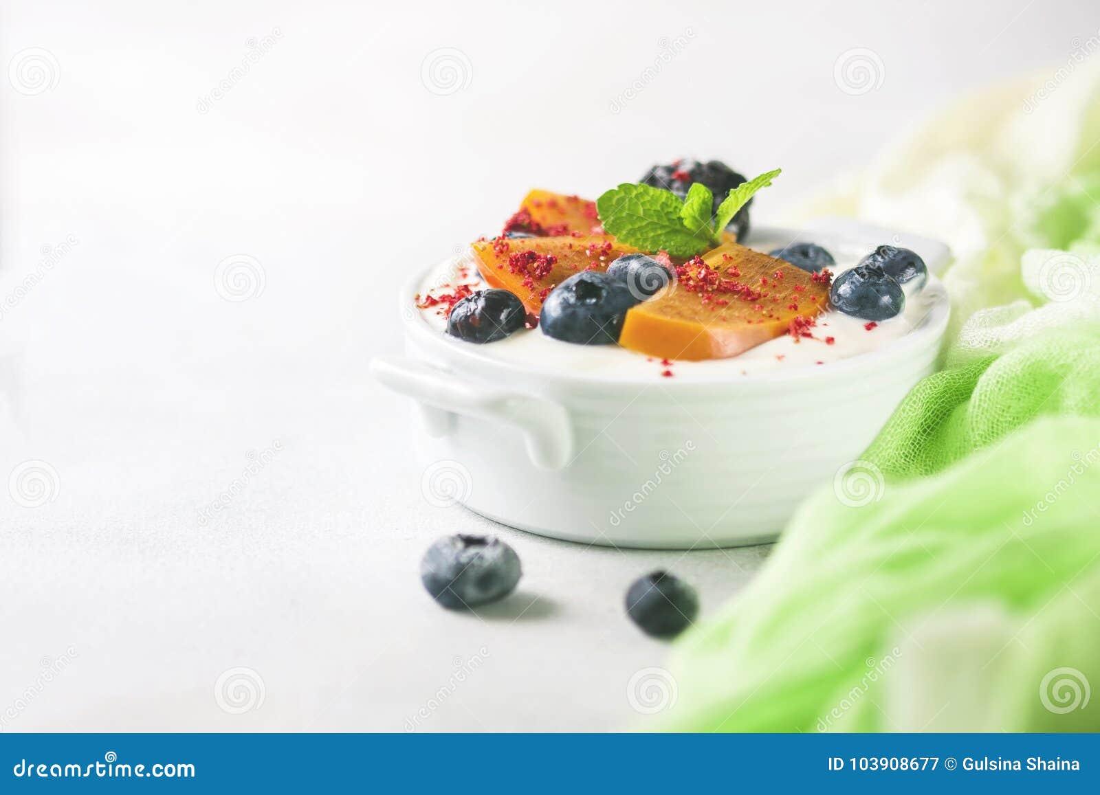 Nourriture saine, casse-croûte ou yaourt grec fait maison de petit déjeuner avec des myrtilles, des mûres, des kakis et la menthe