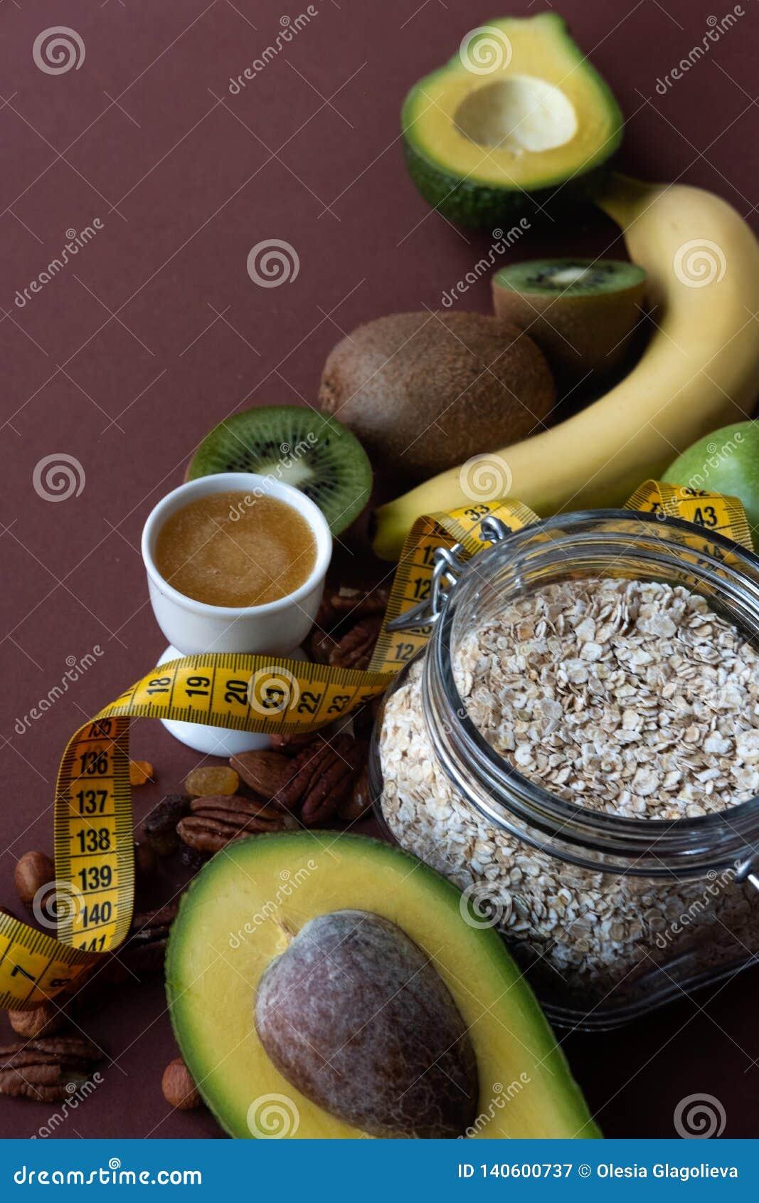 Nourriture saine et ruban métrique jaune au-dessus de table brune Concept de forme physique et de santé